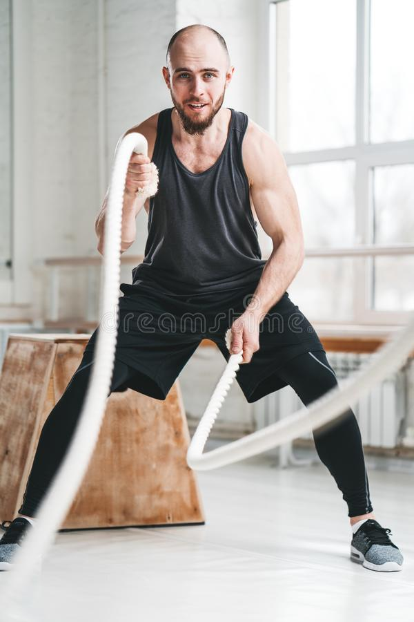 Strong fitness sportsman using training ropes for exercise at gym. Fit man athlete using battle ropes for exercising at light sport hall. Strong fitness stock images