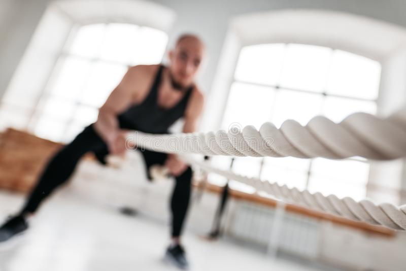 Strong fitness sportsman using training ropes for exercise at gym. Fit man athlete using battle ropes for exercising at light sport hall. Strong fitness royalty free stock image