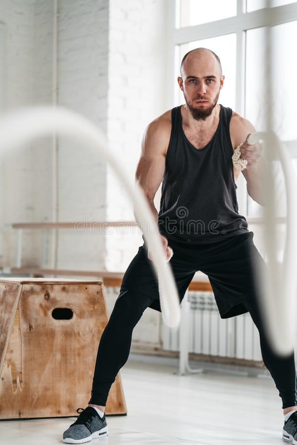 Strong fitness sportsman using training ropes for exercise at gym. Vertical. Fit man athlete using battle ropes for exercising at light sport hall. Strong stock image