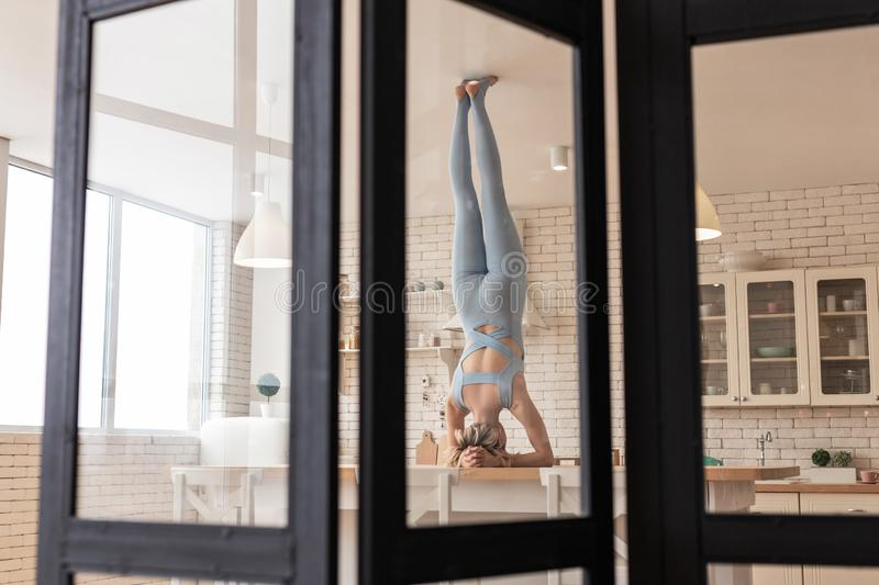 Strong flexible woman displaying her magnificent possibilities. Extraordinary sportive girl. Strong flexible woman displaying her magnificent possibilities while royalty free stock image