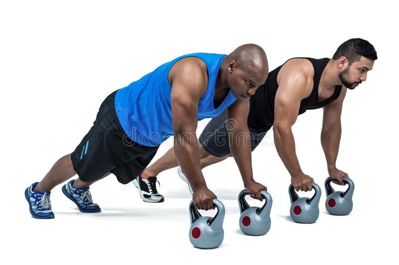 Strong friends using kettlebells together stock photos