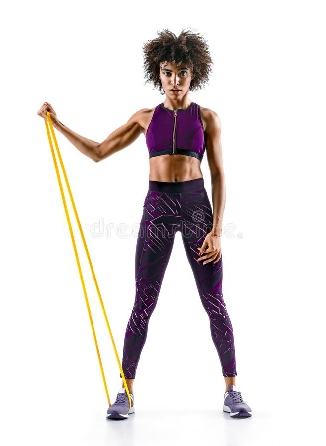 Strong girl using a resistance band in her exercise routine. Young african girl performs fitness exercises on white background. Strength and motivation stock image