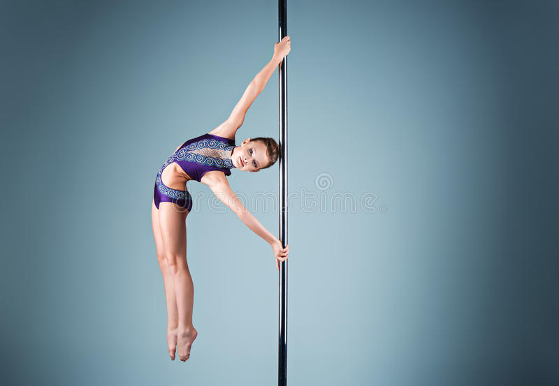 The strong and graceful young girl performing acrobatic exercises on pylon royalty free stock photo