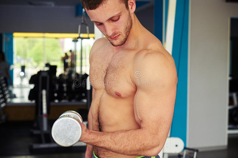 Strong guy with bare chest is flexing biceps royalty free stock photography