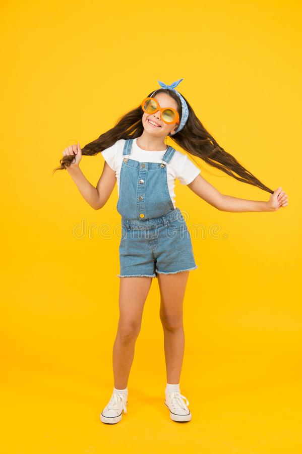 Strong hair. spring kid fashion. cheerful little girl yellow background. retro child long hair. small girl vintage look. Sunglasses. happy childhood. joyful royalty free stock photos
