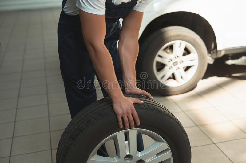 Strong hands of mechanic holding flat tire in car service department.  stock image