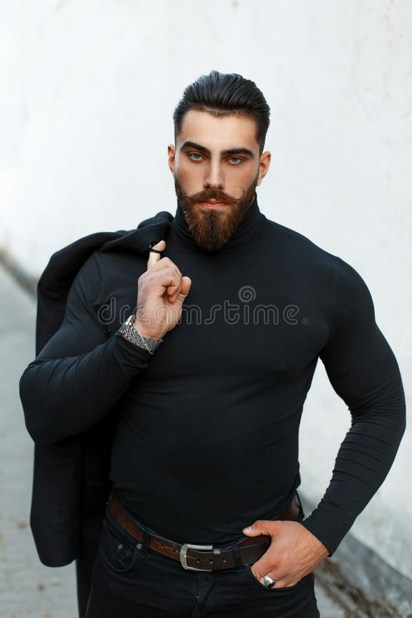 Strong handsome man in a black coat in a black shirt with royalty free stock photo