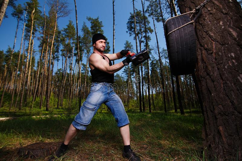 Strong healthy adult ripped man with big muscles hitting car tyr stock photos