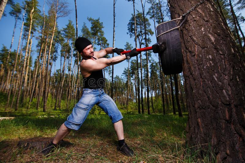 Strong healthy adult ripped man with big muscles hitting car tyr stock images