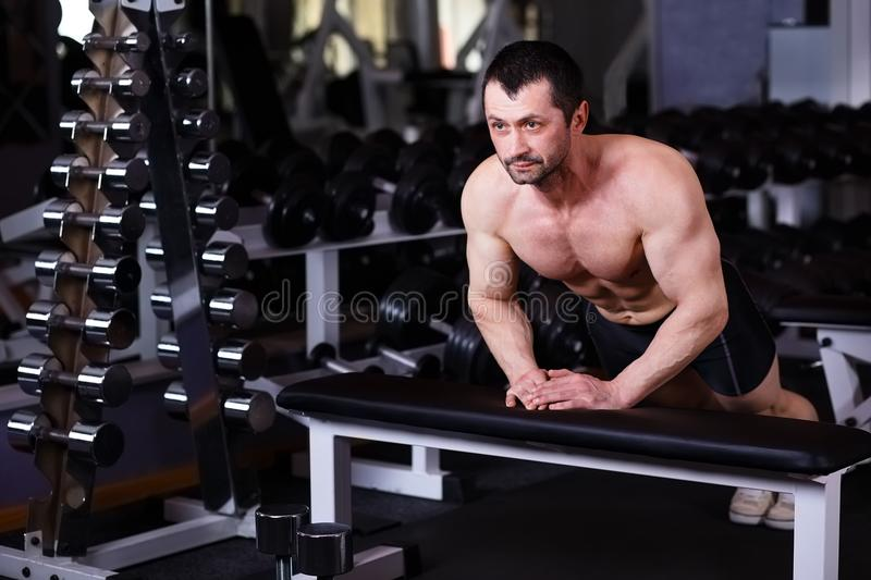 Strong healthy adult ripped man with big muscles pushing up in g stock image