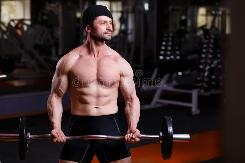 Strong healthy adult ripped man with big muscles training with b royalty free stock photography