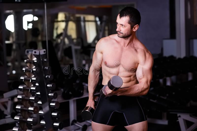 Strong healthy adult ripped man with big muscles training with d stock photos