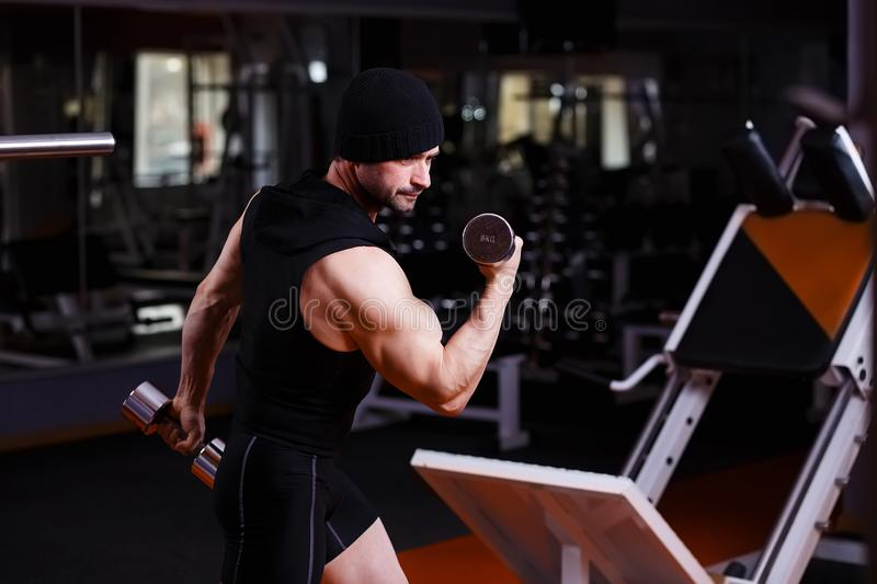Strong healthy adult ripped man with big muscles training with d royalty free stock image