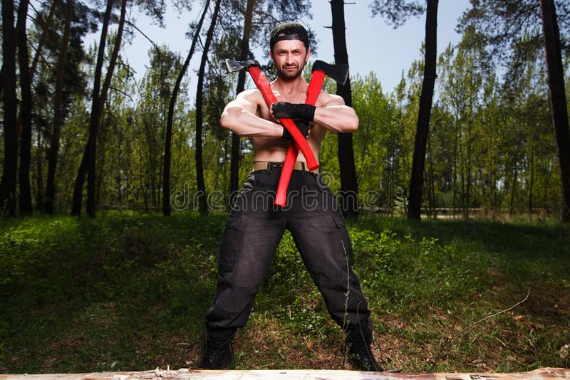 Strong healthy adult ripped man lumberjack worker standing in th stock images