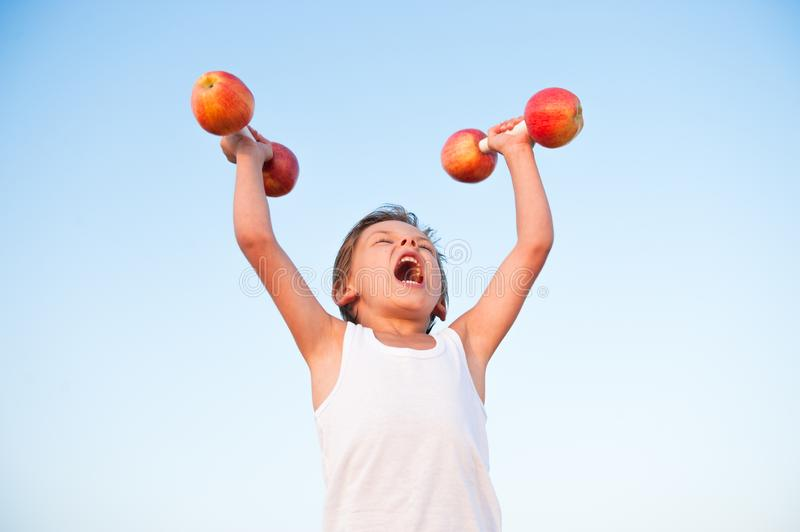 Strong healthy kid in white shirt lifting dumbbells made from ap. Strong healthy cute caucasian kid in white shirt lifting dumbbells made from fresh apples royalty free stock photo