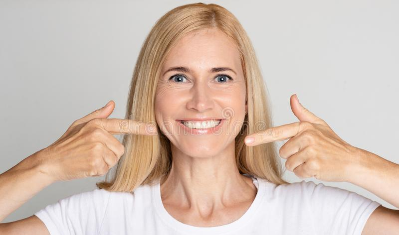 Strong healthy teeth. Woman pointing on her perfect smile stock image