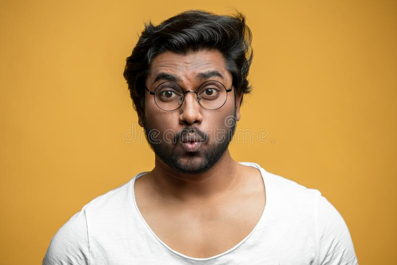 Strong Indian guy is learning to whistle. Male who has lips like a jigsaw puzzle. hindoo singer warming up stock photography