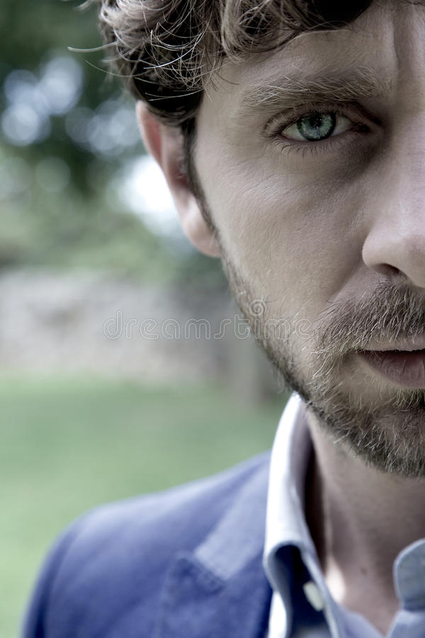 Strong intense expression of man with blue eyes portrait. Cool man looking camera with strong expression royalty free stock images