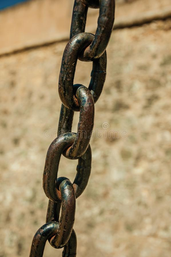 Strong iron chain links in front of stone wall royalty free stock photography