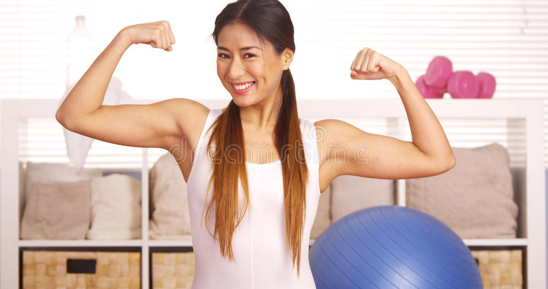 Strong Japanese woman showing off muscles. Strong Asian woman showing off muscles royalty free stock photography