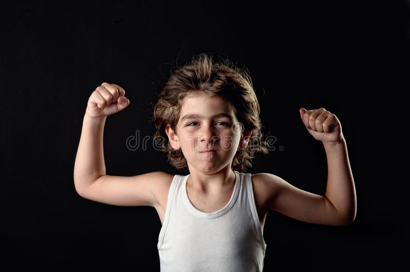 Strong Kid showing his muscles. Against a black background royalty free stock images