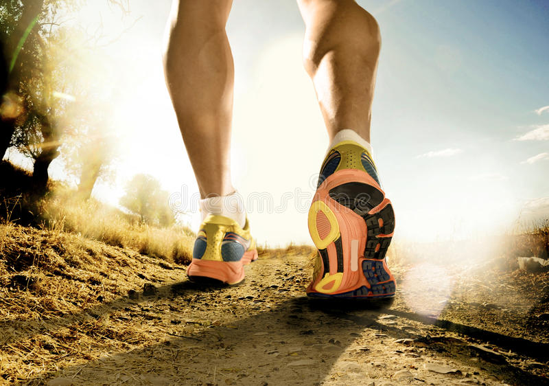 Strong legs and shoes of sport man jogging in fitness training workout on off road stock photography