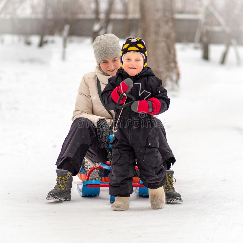 Strong little boy carries his mother on a sled royalty free stock image