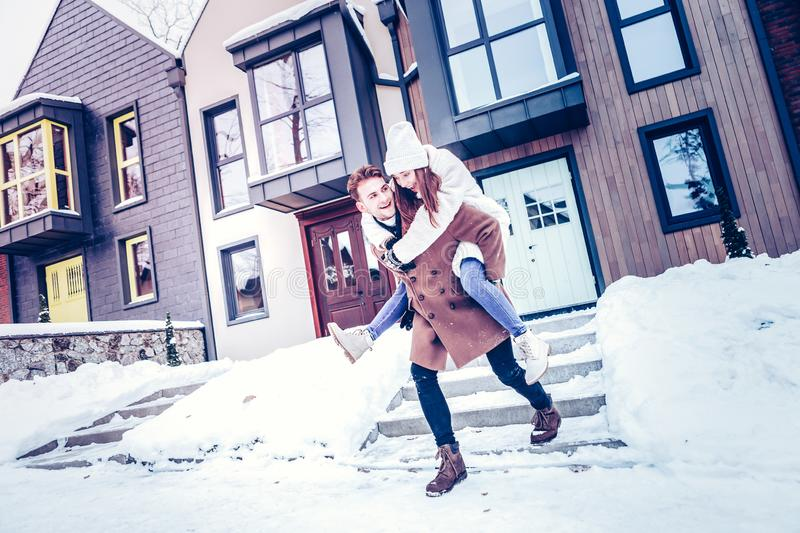 Strong loving man holding his stylish wife on his back royalty free stock photography