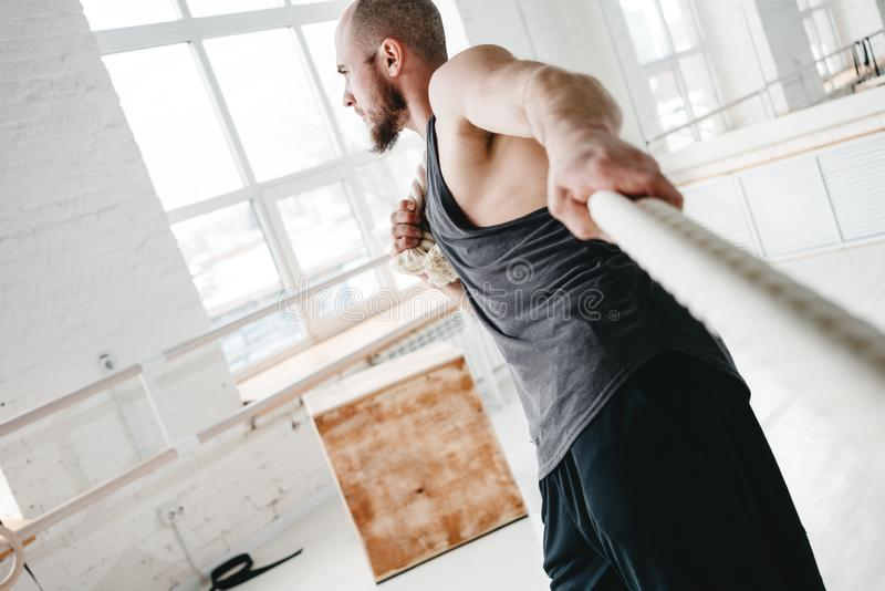 Strong male athlete doing exercises with rope at cross gym. Working out with battle ropes at cross gym stock image