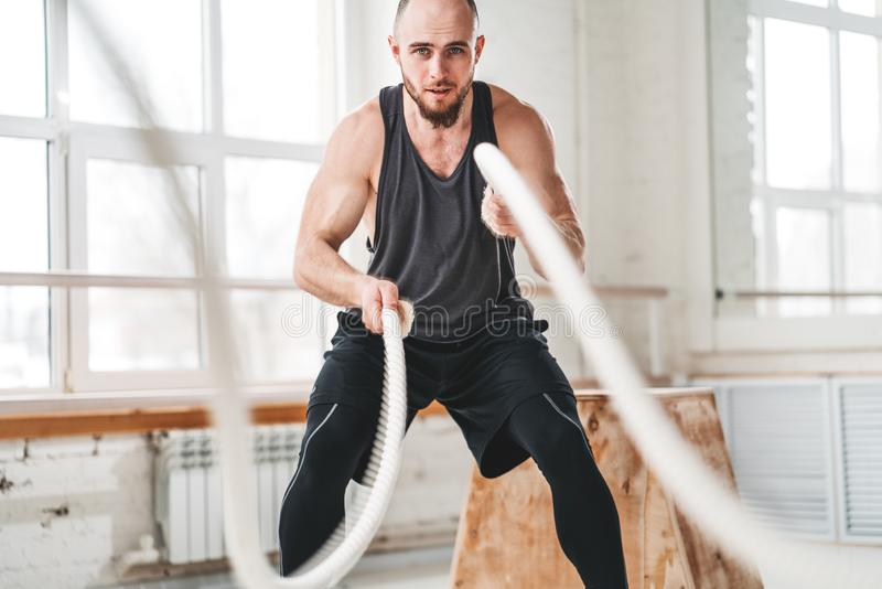 Strong male athlete doing exercises with rope at gym. Working out with battle ropes at cross gym stock images