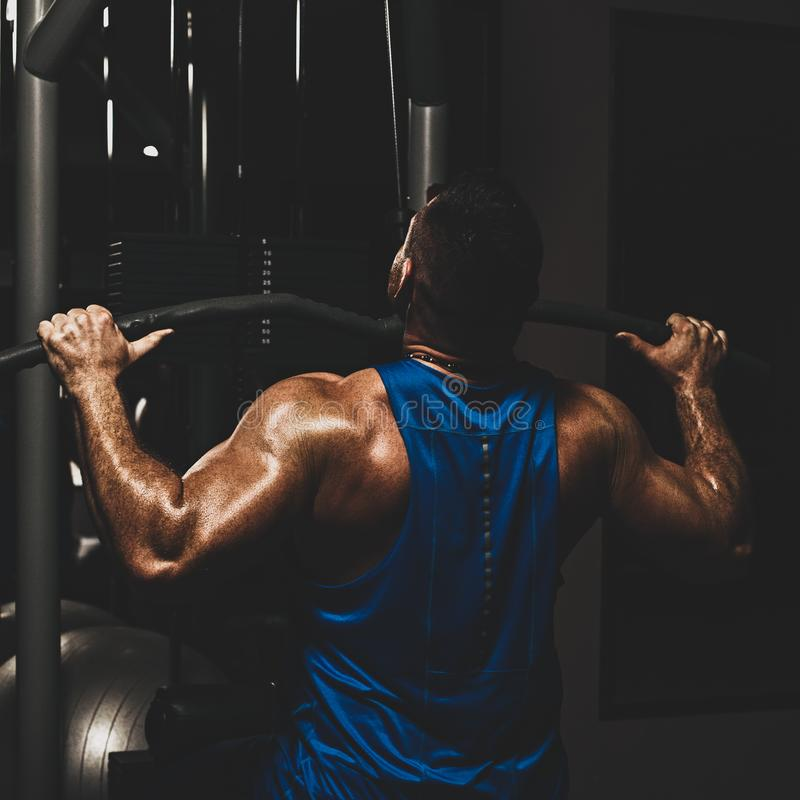 Lat pulldown exercise. Strong male bodybuilder doing exercise for back with lat pulldown machine in gym, with color imitating social network filter royalty free stock photos