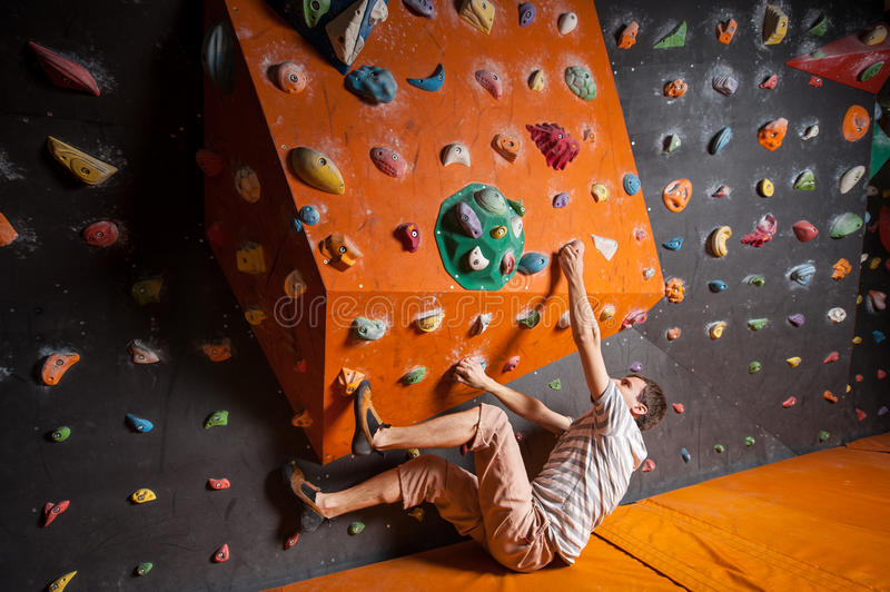 Strong male climber on boulder climbing wall indoor. Rock climber starting to practice artificial rock climbing on a rock wall indoors, without special equipment royalty free stock photo