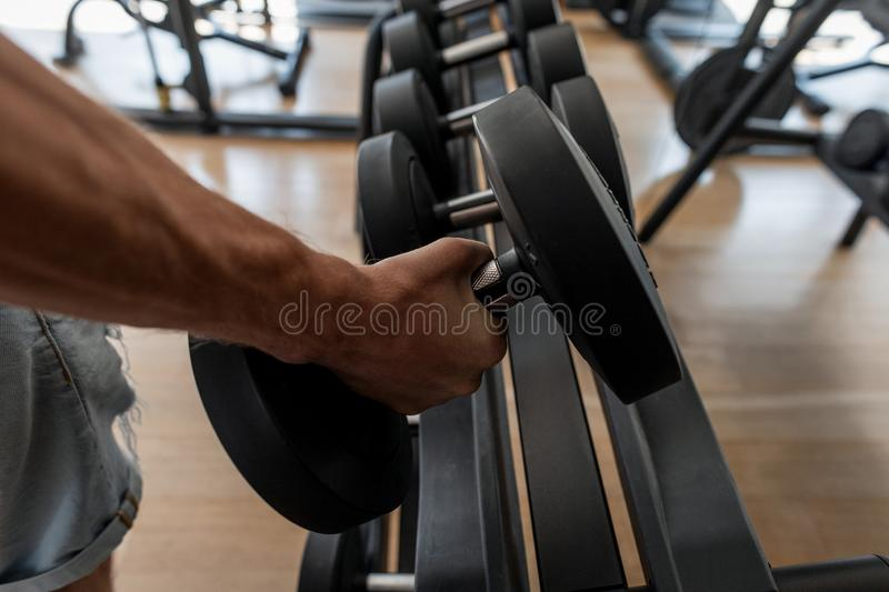 Strong male hand lifting a dumbbell in a sports studio. Athletic young man trains in the gym. Close-up of a man`s hand royalty free stock image