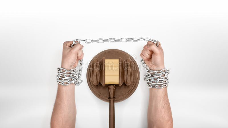 Strong male hands straining a metal chain capturing them around a judge gavel. royalty free stock photography