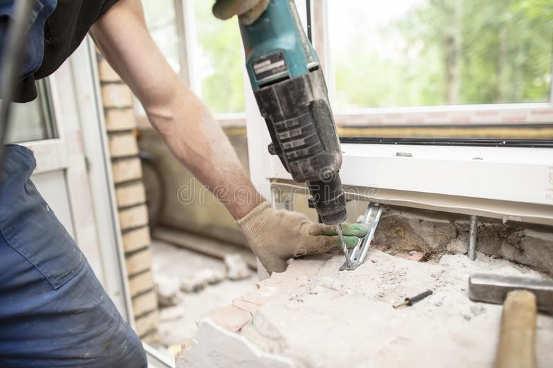 Strong male hands of a worker hold an electric perforator drill in their hands with the help of which it make a hole in a brick. Wall to install and fix a PVC royalty free stock images