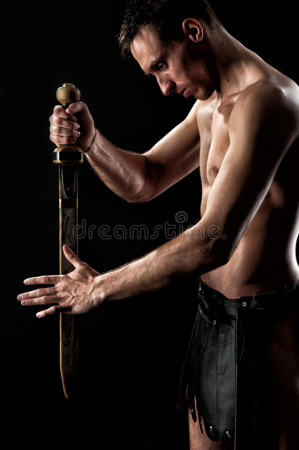 Download Strong Man With Ancient Sword And Armor On The Black Background Stock Photo - Image: 56207662
