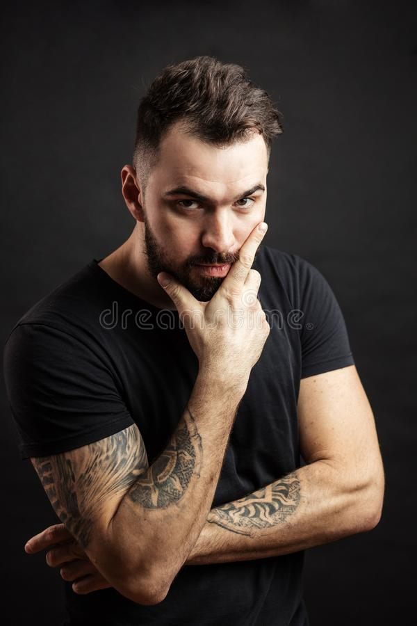 Strong man in black tight fitted shirt with a serious expression on his face. royalty free stock photography