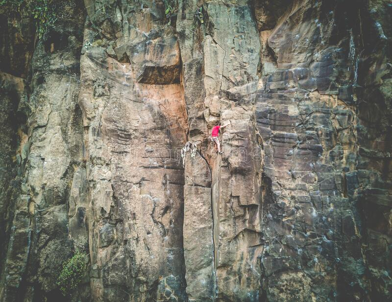 Strong man climbing a rock wall in a canyon - Climber training outdoor in a rocky spot - Travel, adrenaline and extreme dangerous. Sport concept - Focus on him royalty free stock photos