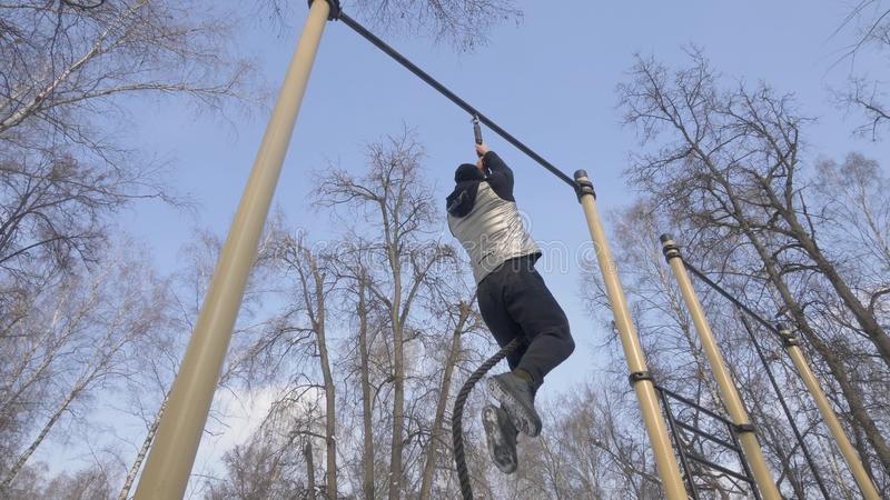 Strong man climbing on rope during outdoor workout on sport ground stock image