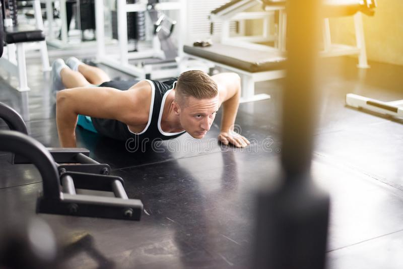 Strong man doing push up and exercises on floor at gym stock photography