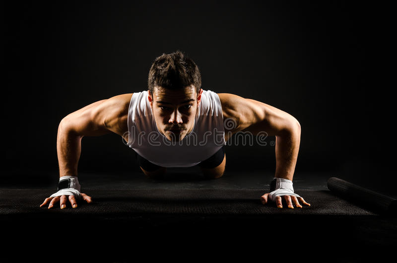 Strong man doing push-ups. Strong determined fit man doing push-ups on a mattress royalty free stock images