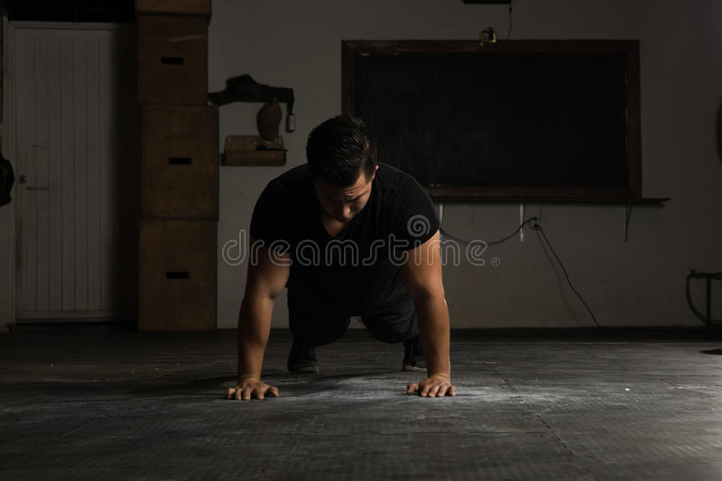 Strong man doing push-ups in a gym royalty free stock photos