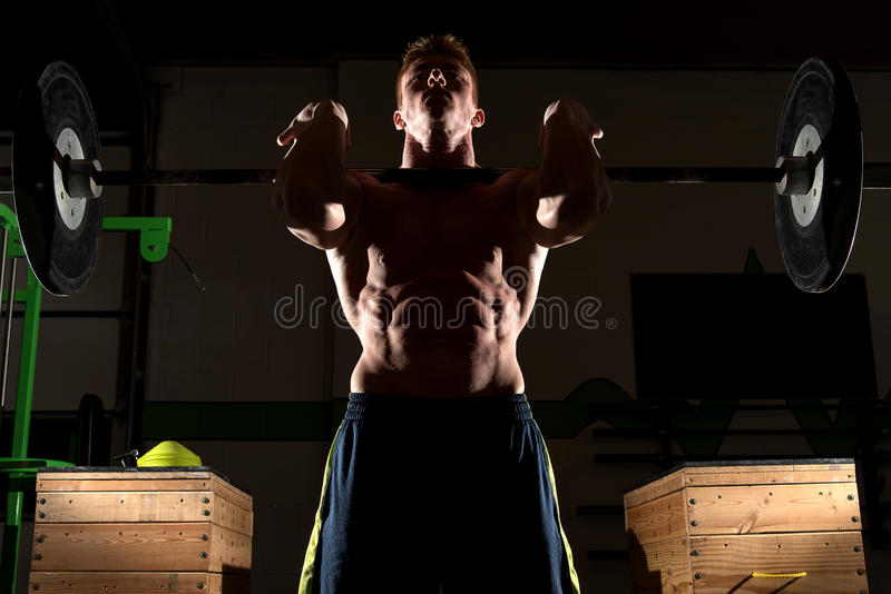Strong man exercising in dramatic light. This is a dramatic image of a really strong man at a gym working out and exercising and showing off his muscles. The royalty free stock images