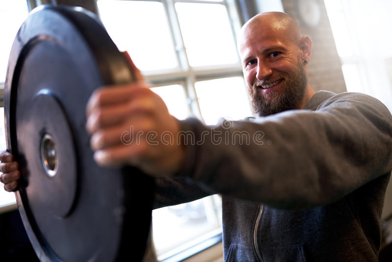 Strong man lifting weight plate stock photo