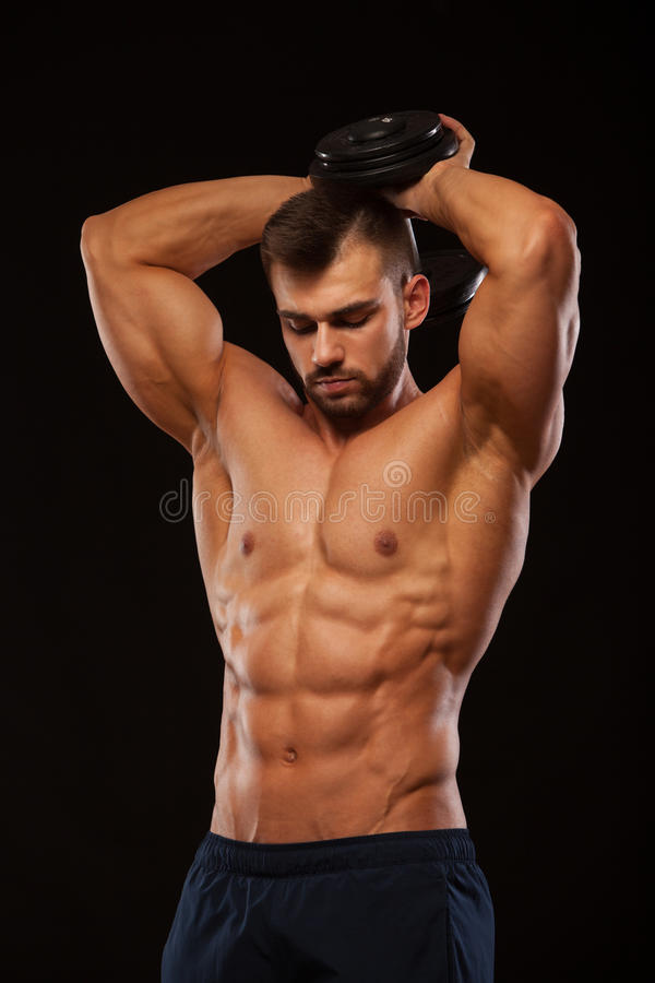 Strong man making exercises on triceps with a dumbbell. Close up shot training hands. Fitness Model showing his Torso stock photos