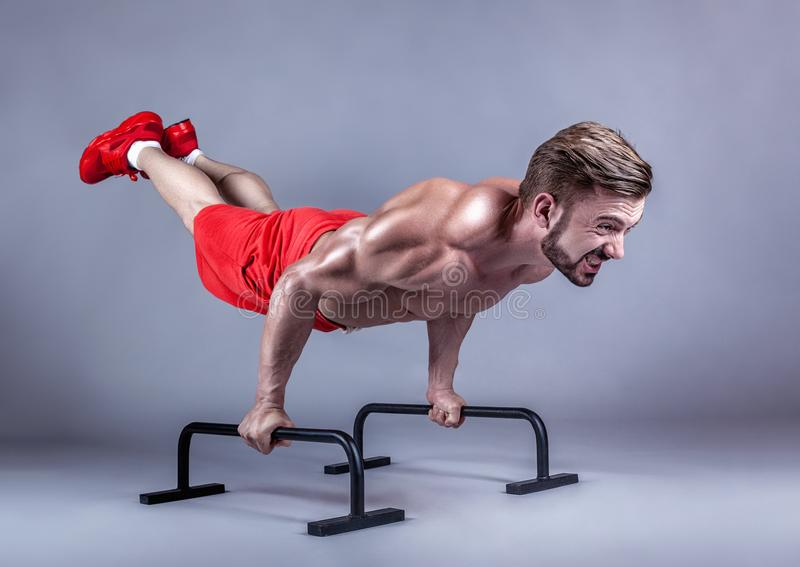 Strong man. Strong male athlete shows calisthenic moves extended legs planche push ups on parallel bars, studio shot royalty free stock image