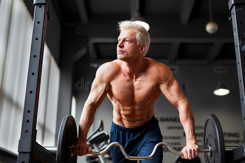 Strong man with muscular body working out in gym. Weight exercise with barbell in fitness club. royalty free stock photo