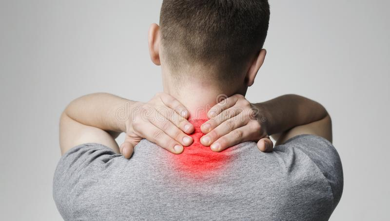 Strong man with neck pain, back view. Millennial man suffering from pain in neck. Symptom of cervical chondrosis, back view stock photos