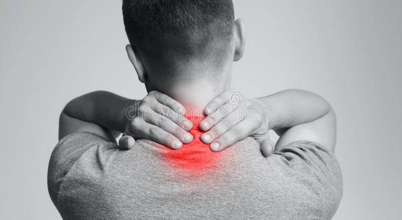 Strong man with neck pain, back view. Young man suffering from pain in neck. Inflammation of vertebra, back view stock photo