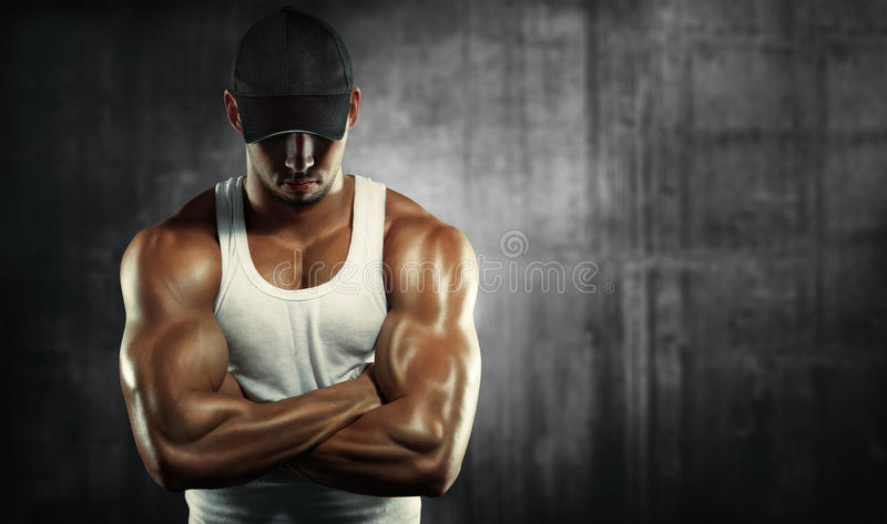 Strong man posing on a concrete background stock images